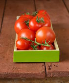 Fresh ripe organic tomatoes on a wooden table — Foto de Stock