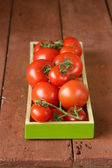 Fresh ripe organic tomatoes on a wooden table — Stock Photo
