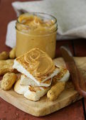 Homemade peanut butter with whole nuts on a wooden table — Stok fotoğraf