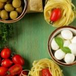 Italian still life - olives, mozzarella cheese, pasta, tomatoes — Stock Photo #44553065