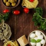 Italian still life - olives, mozzarella cheese, pasta, tomatoes — Stock Photo #44553075