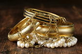 Gold and pearl jewelry on vintage wooden background — Stock Photo