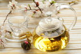 Glass teapot with exotic green tea on a wooden table — Stock Photo