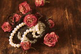 Vintage pearl with dry roses on a wooden background — Stock Photo