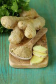 Ground ginger in a wooden spoon, fresh root in the background — Stock Photo