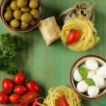 Italian still life - olives, mozzarella cheese, pasta, tomatoes — Stock Photo