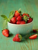 Fresh sweet ripe strawberries in a bowl on a wooden table — Stock Photo