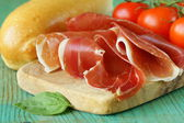 Parma ham (jamon) sliced on a wooden board — Stock Photo
