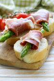 Delicacy appetizer green asparagus and smoked ham — Stock Photo