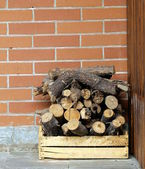 Dry chopped firewood logs in a pile on the brick wall background — Stock Photo