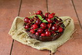 Fresh red ripe cherries in wicker basket on a wooden table — Stock Photo