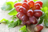 Branch of red ripe grapes with green leaves on a wooden table — Foto Stock