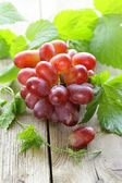 Branch of red ripe grapes with green leaves on a wooden table — Stock Photo