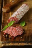 Delicacy smoked sausage (salami) on a wooden board — Stock Photo