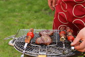 Cooking on the barbecue grill assortment sausages steak and skewers — Stock Photo