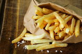 Traditional potatoes French fries with salt on wooden background — Stockfoto