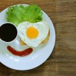 Funny face serving breakfast, fried egg, toast and green salad — Stock Photo
