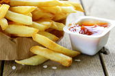 Traditional potatoes French fries with salt on wooden background — Foto Stock