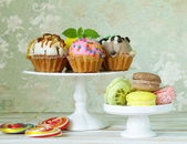 Holiday desserts, decorated cupcakes and colorful macaroons — Stock Photo
