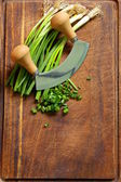 Fresh green chives on wooden board with a special knife — Stock Photo