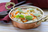 Rice with vegetables cooked in Indian style in a copper pan — Stock Photo
