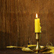 Vintage candlestick with candle on the wooden background — Stock Photo #49543371