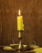 Vintage candlestick with candle on the wooden background — Stock Photo