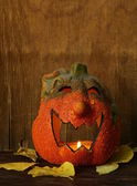 Halloween still life - pumpkin with  yellow leaves on the wooden background — Stock Photo