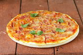Traditional Italian pizza with prosciutto ham and basil — Stock Photo