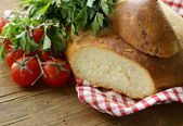 Traditional Italian ciabatta bread with tomatoes and herbs — Stock Photo