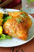 Baked chicken leg with corn for garnish — Stock Photo