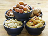 Different kinds of nuts (almonds, walnuts, hazelnuts, peanuts) in a bowl on a wooden table — Stock Photo