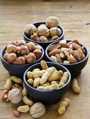 Diferentes tipos de nozes (amêndoas, nozes, avelãs, amendoins) em uma tigela sobre uma mesa de madeira — Fotografia Stock