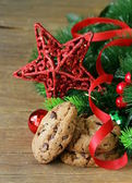 Cookies with chocolate on a wooden background with Christmas tree branches and decorations — Stock Photo