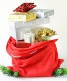 Red bag full of Christmas gifts, boxes and decorations — Stock Photo