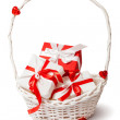 Cute red and white gift boxes in white basket. — Stock Photo