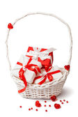 Cute red and white gift boxes in white basket. — Zdjęcie stockowe