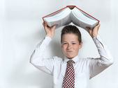 Displeased schoolboy throws big book — Stock Photo