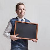 Cute schoolboy with empty chalkboard — Stock Photo