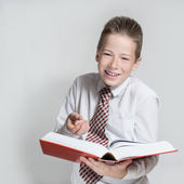 Smiling schoolboy reads a big red book — Stock Photo