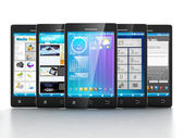Mobile applications. Group of mobile phones are frontally on a w — Photo