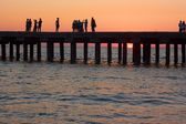 People on the old sea pier at sunset — Stock Photo