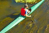 Canoeist floating on the overgrown river — Stock Photo