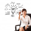 Young business woman drawing light bulb with various diagrams an — Stock Photo #14580149