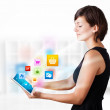 Young woman looking at modern tablet with colourful icons — Foto Stock