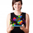 Young woman looking at modern tablet with pie charts — Stock Photo #14580443