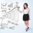 Young business woman drawing diagrams on whiteboard — Stock Photo