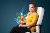 Young woman looking at modern tablet with abstract lights and va — Stock Photo