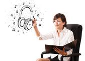 Giovane ragazza disegno cuffia e note musicali — Foto Stock
