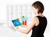 Young woman looking at modern tablet with colourful diagrams — Stock Photo